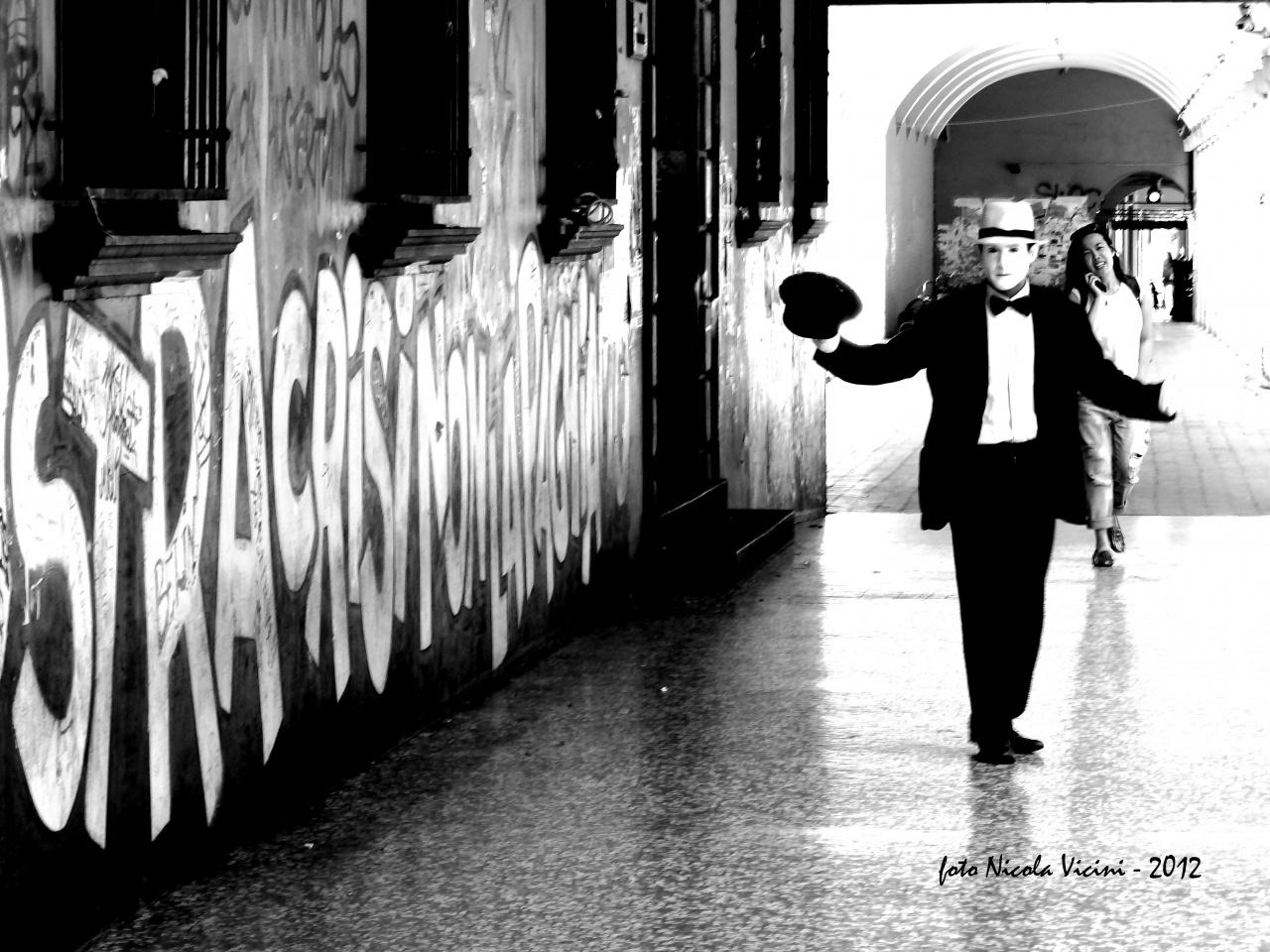 il mimo - Reportage a Bologna, 30 Maggio 2012  Camminando sotto ai portici, cercando di raccontare in un immagine  uno dei momenti del quotidiano di questa splendida città. Tre soggetti, il murale, il mimo e la ragazza sorridente col telefonino  raccontano tre storie differenti